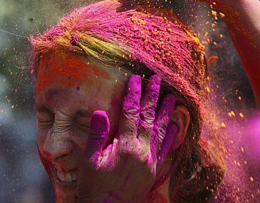 A girl reacts as she is smothered in coloured powder while celebrating Holi in Hyderabad