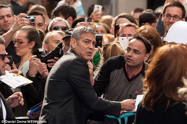 George Clooney signs autographs