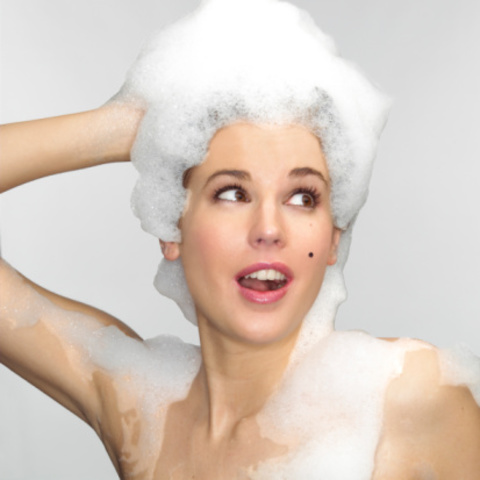 Young woman with shampoo in hair